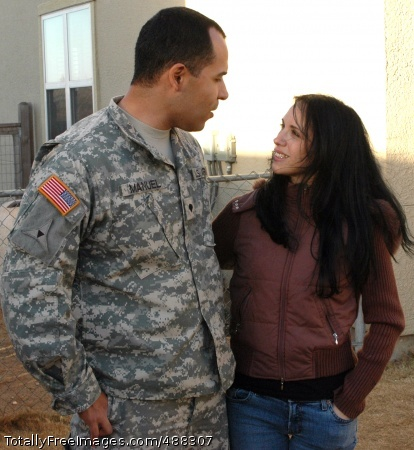Spc. Alex Manuel and his wife, Veronica Manuel, talk in their back yard as their children play.  It took time for Alex to start feeling normal at home again after his 14 months in Iraq, but with the support of his loving family, the situation has gotten better, he said. Photo Credit: Feb 4, 2008