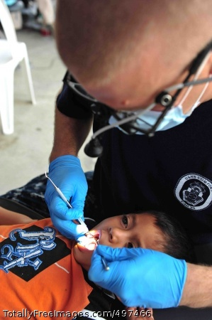 110715-F-NJ219-256 ACAJUTLA, El Salvador (July 15, 2011) Lt. Cmdr. Michael Rudmann, a dentist from Derwood, Md., cleans a patient's teeth during a Continuing Promise 2011 community service medical project at the Polideportivo medical site. Continuing Promise is a five-month humanitarian assistance mission to the Caribbean, Central and South America. (U.S. Air Force photo by Staff Sgt. Courtney Richardson/Released)