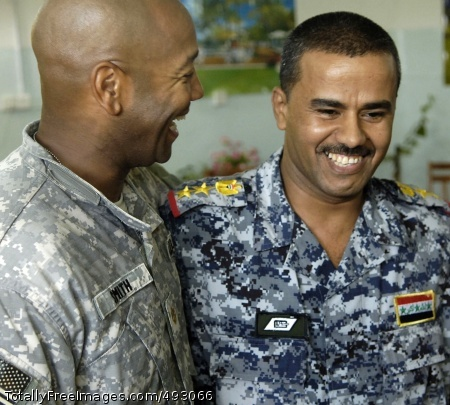 Law Enforcement Maj. E. E. Smith, National Police Transition Team, and Iraqi National Police Col. Ahmed Hatem Hamid Taher, embrace after a successful humanitarian mission in Al Furat, May 24.  Photo Credit: Jun 11, 2007