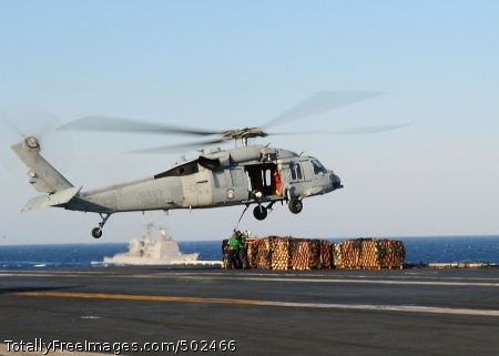 110328-N-SG869-016 PACIFIC OCEAN (March 29, 2011) Sailors assigned to the supply department of the aircraft carrier USS Ronald Reagan (CVN 76) hook a pallet of supplies to an MH-60S Sea Hawk helicopter from the Wild Cards of Helicopter Sea Combat Squadron (HSC) 23. The Ticonderoga-class guided-missile cruiser USS Chancellorsville (CG 62) is in the background. Ronald Reagan is providing humanitarian assistance to Japan as directed in support of Operation Tomodachi. (U.S. Navy photo by Mass Communication Specialist 2nd Class Josh Cassatt/Released)