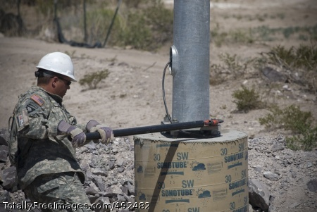 Border Duty Spc. Zachary Nutt tightens bolts on the newly installed light post. Photo Credit: Jul 17, 2007