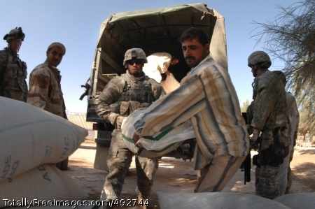 Ready to Help or Sgt. Richard Elerick and an Iraqi man unload humanitarian relief supplies for the villagers. Photo Credit: Jun 28, 2007