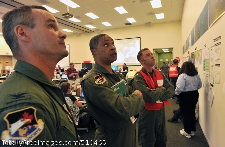 OUMA, La. - (left to right) Col. Jeff Fiebig, the mobilization assistant to the commander, First Air Force, Tyndall AFB, Fla., Maj. Gen. Garry Dean, the joint force air component commander for North American Aerospace Defense Command and U.S. Northern Command, and Cmdr. Drew Cromwell, air operations branch chief for the Houma Incident Command Post, analyze safety information in the operations center in the central operations room, June 15, 2010. Dean visited the command post to discuss ways the Air Force can assist in the Gulf for the nation's largest oil spill response and recovery.