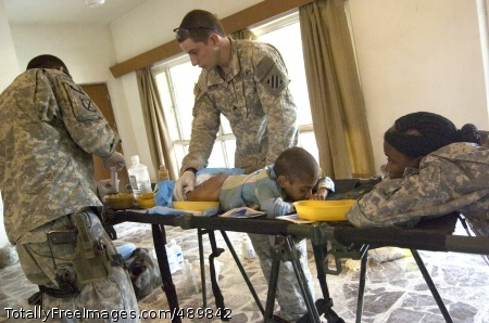 Soldiers Provide Sgt. Daniel Woods, right, and Spc. Fabio Henriques prepare to clean a young boy's wounds as Sgt. Catrina Downing comforts him during a medical aid mission in Arab Jabour, southern Baghdad. The Soldiers are with the 3rd Infantry Division. Photo Credit: Nov 14, 2007