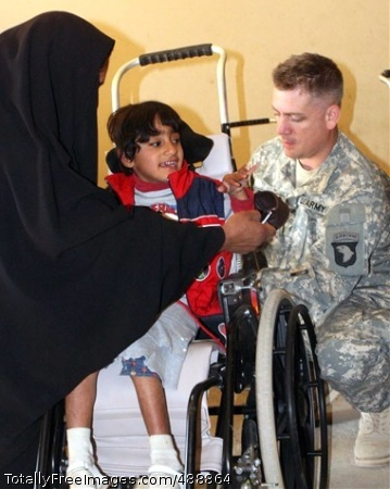 Iraqi Children Get Sgt. Lonnie Todero, a medic with 1st Squadron, 33rd Cavalry, 3rd Brigade Combat Team, 101st Airborne Division (Air Assault), makes adjustments to Zeanib Saad Al Amary's wheelchair Dec. 13, 2007, at Radwaniyah Palace Complex Civil-Military Operations Center in Iraq.  Photo Credit: Dec 27, 2007