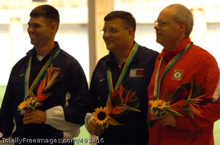 Soldiers Win Gold, U.S. Army Marksmanship Unit Sgt. 1st Class Thomas Tamas (center) celebrates winning the gold medal in the men's 50-meter rifle prone shooting event July 17 at the XV Pan American Games in Rio de Janeiro, Brazil. Spc. Michael McPhail (left) won the silver medal and Canada's Gale Stewart (right) took the bronze. Both Soldiers are stationed at Fort Benning, Ga.  Photo Credit: Jul 19, 2007