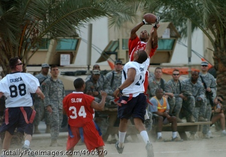 The 'NFC's' Christopher Thomas leaps up above the 'AFC's' Brandon Jones to haul in a pass during the second half of the Black Jack Flag Football All-Star Game held on Forward Operating Base Prosperity in central Baghdad Oct. 20.  Photo Credit: Oct 24, 2007