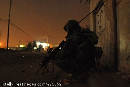 Soldier Silhouettes Spc. Herrick Lidstone, a radio operator with Company B, 2nd Battalion, 325th Airborne Infantry Regiment, 2nd Brigade Combat Team, 82nd Airborne Division, takes a security halt during a nighttime foot patrol in Sha'ab, Baghdad, May 4. Photo Credit: Jun 7, 2007