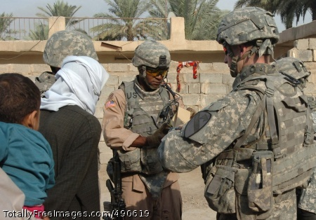 Philadelphia native Staff Sgt. Halisaam Thompson (center) and Sgt. Ken Thomas (right), who hails from Utopia, Texas, both scouts with Troop C, 1st Squadron, 7th Cavalry Regiment collect census information Oct. 6 from a local Iraqi family in the Baghdad Gardens area near Taji, Iraq that lies just on the edge of Baghdad.  Photo Credit: Oct 10, 2007