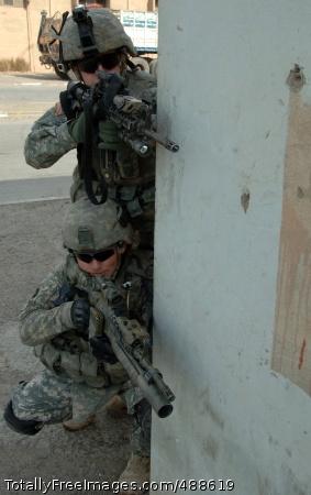 Patrolling Baghdad Sgt. Joseph Chamberlain and Spc. Alex Egan peer around a corner. Photo Credit: Jan 14, 2008